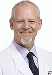 Dr. Russell Greenfield smiles in a white lab coat