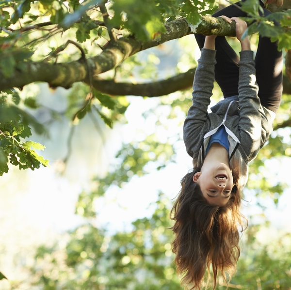 Young girl hanging upside down branch