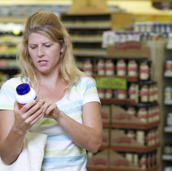 Woman in Store Examines Supplements
