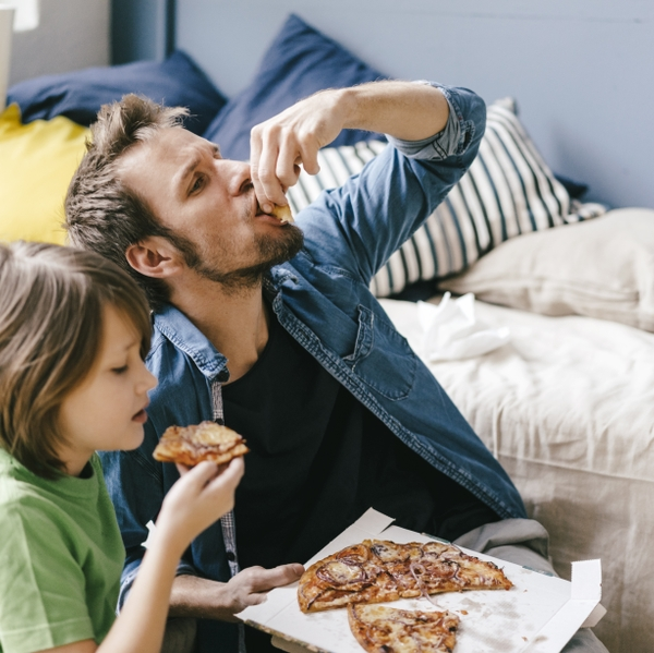 Father and son eating pizza at home