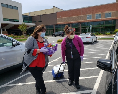Jamie Vogler and Jo Burleson provide snacks to family members in the parking lot at Novant Health Clemmons Medical Center