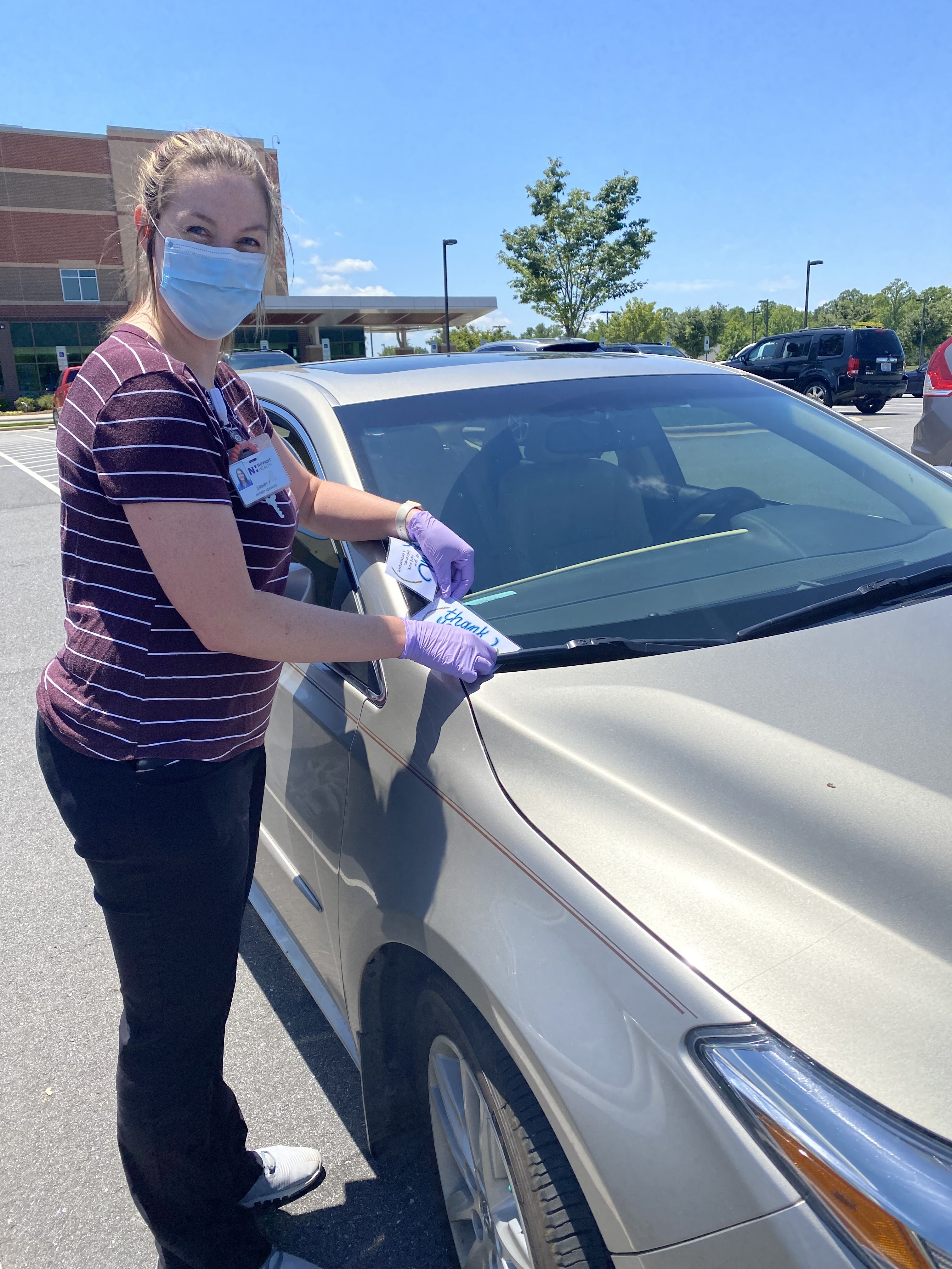 Sidney Yates places a card of encouragement on a car at Novant Health Clemmons Medical Center
