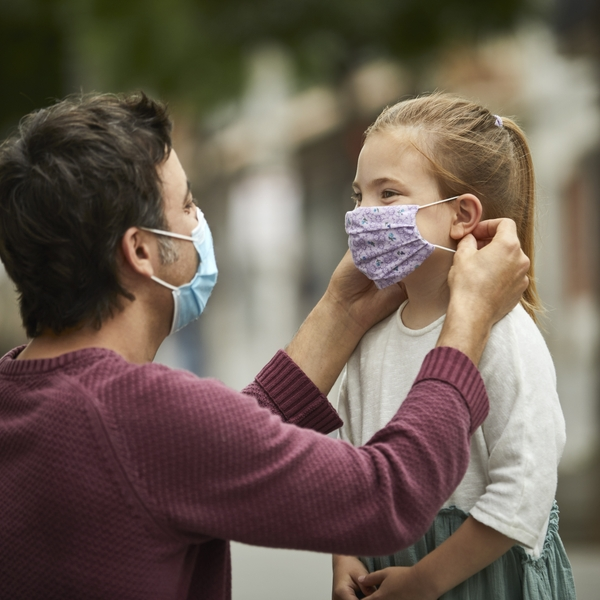 Father helps daughter with mask