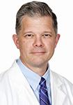 Dr. David Priest smiles in white lab coat