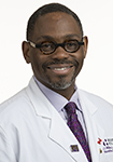 Dr. Jerome Williams Jr. smiles in a white lab coat.