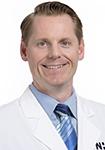 Dr. Justin Kauk smiles in a white lab coat.