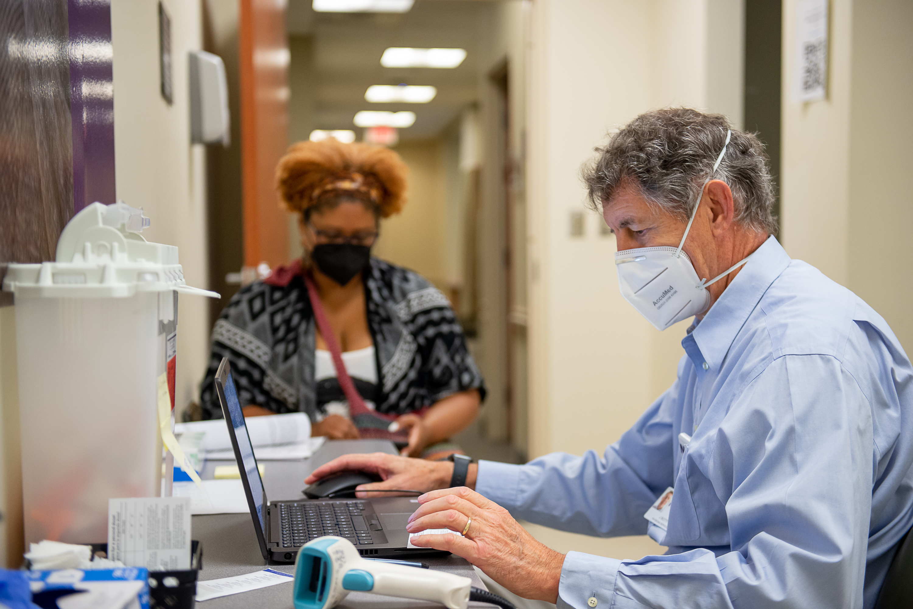 Dr. John Botti talks with a black woman before she gets the COVID-19 vaccination.