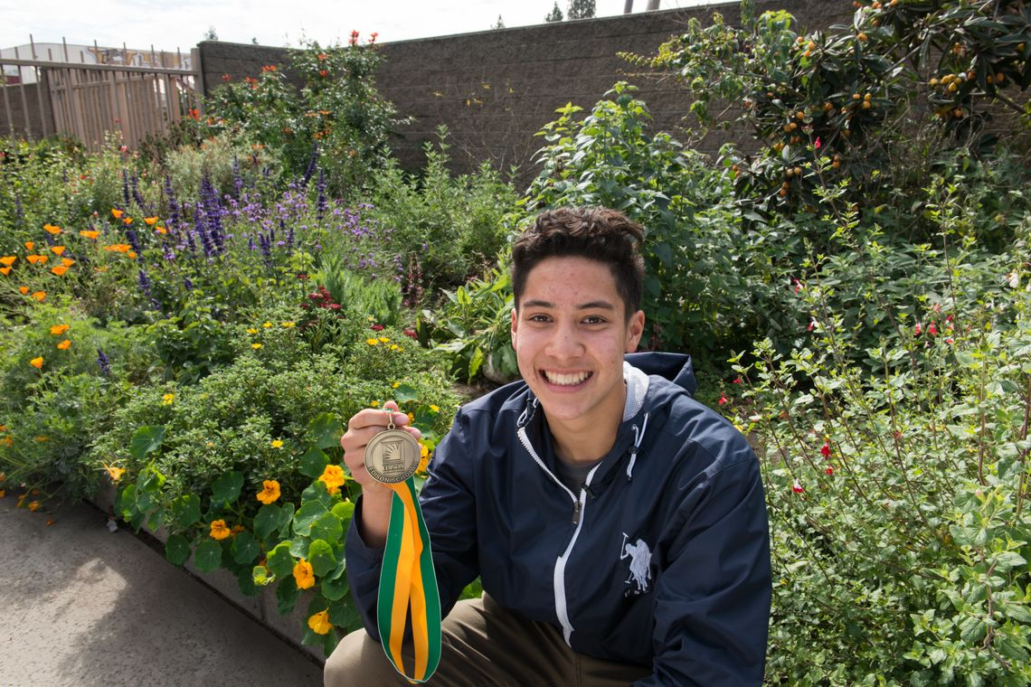 Edison Scholar Justin Hogenauer in front of a sustainable garden he helped build at his school.