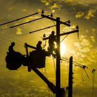 Linemen Work on Poles at Sunset