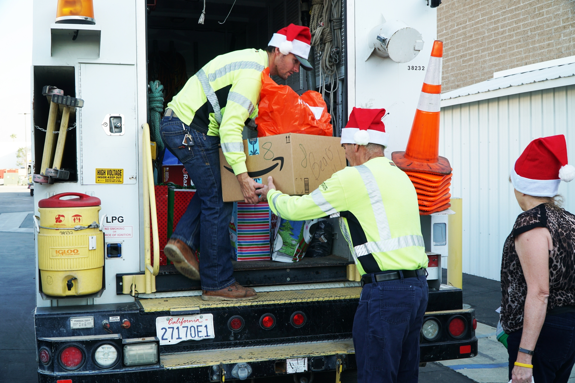 SCE groundman Aaron Crosby loads Christmas gifts to deliver to foster children at Specialized Care Foster Family Agency.