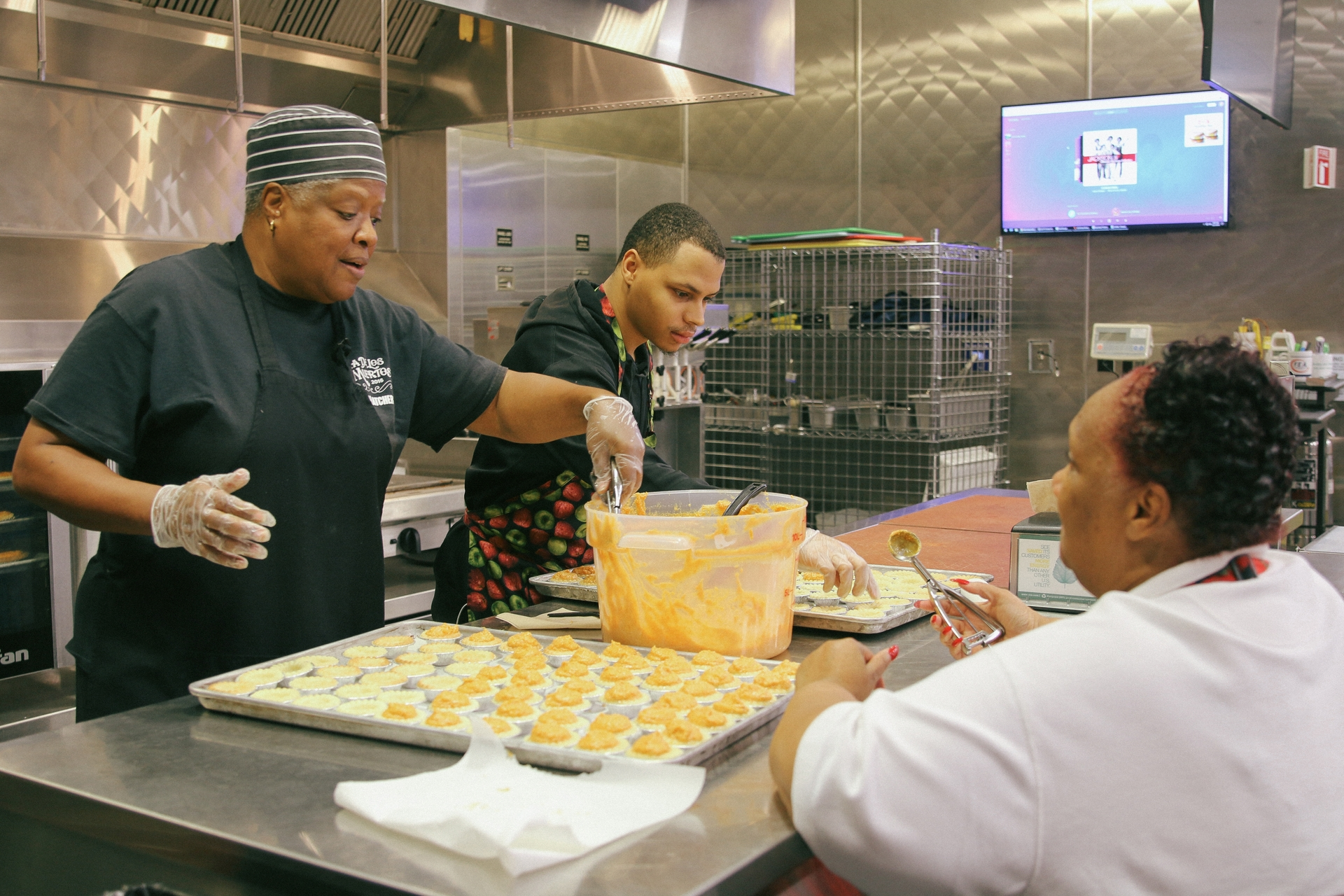 Cherie Beasley (right) and two volunteers prepare hundreds of tartlets to give to homeless families.