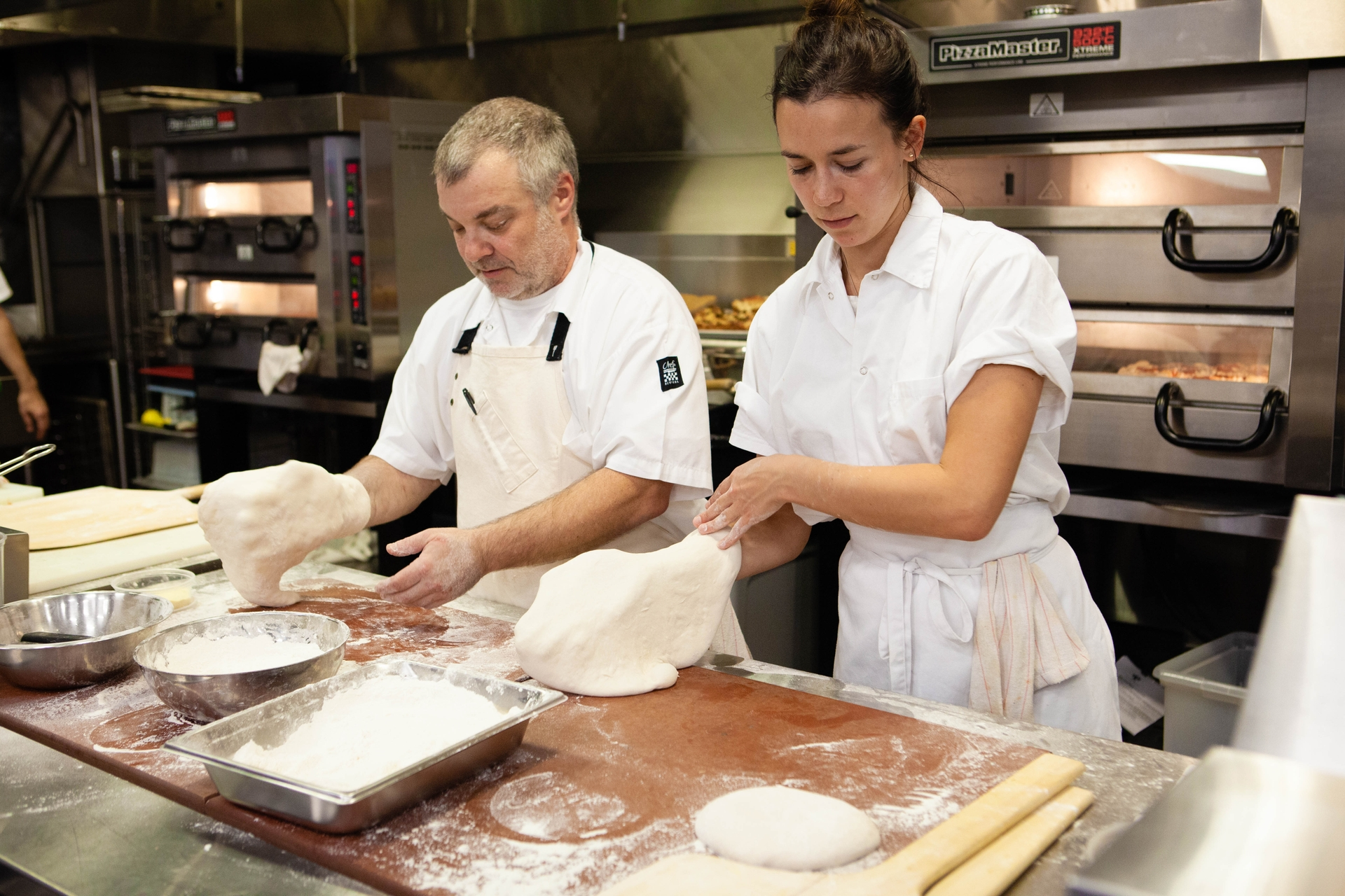 Pizza chefs Noel Brohner and Ines Barlerin prepare pizza dough at SCE's Foodservice Technology Center reopening.