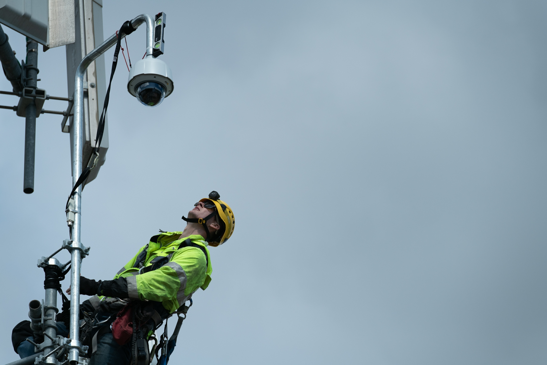 A worker looks up at a wildfire monitoring camera to ensure it was mounted properly.