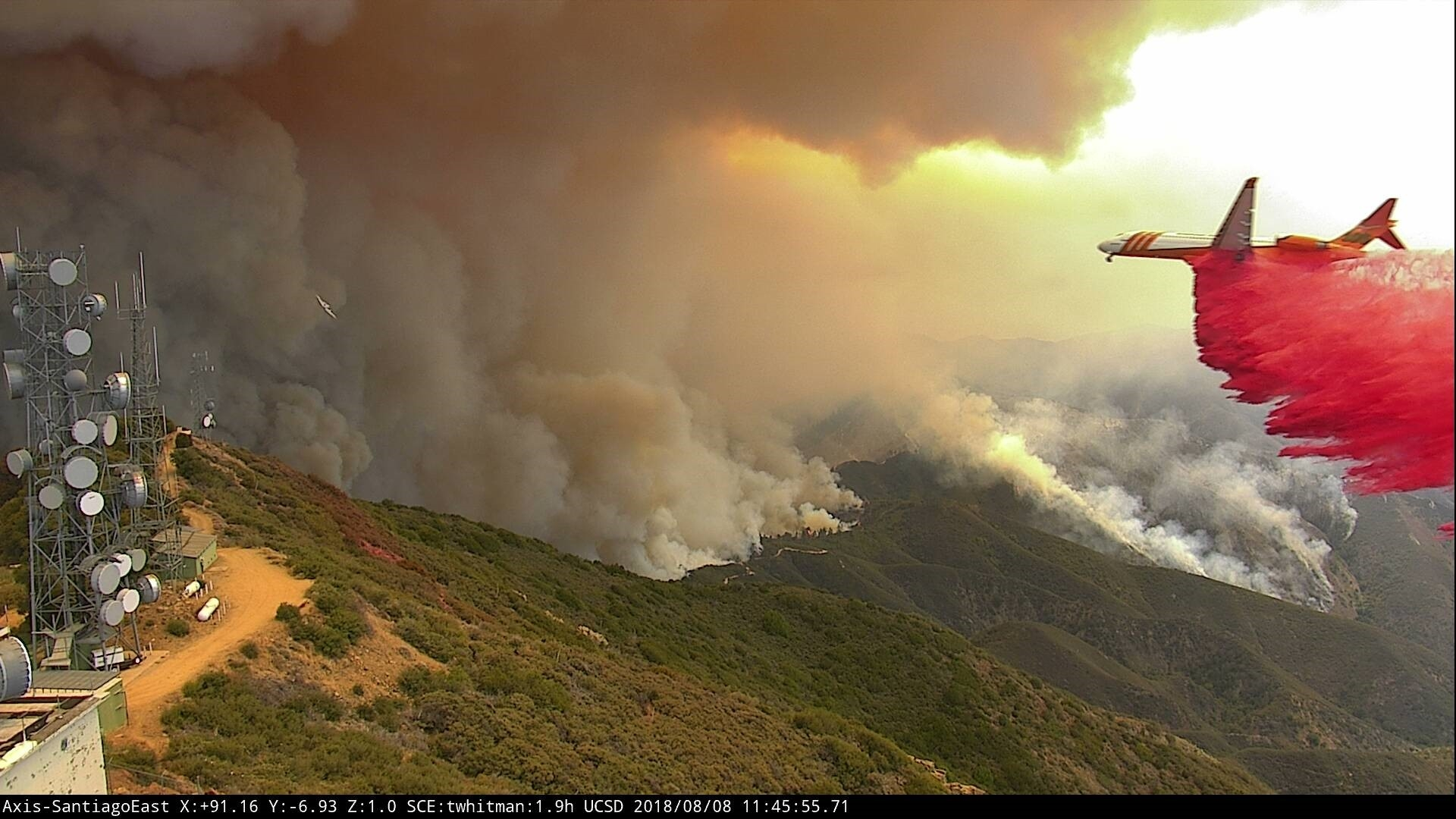 A plane drops fire retardant on the Holy Fire near Santiago Peak captured by a HD SCE camera connected to UCSD's wildfire camera network.