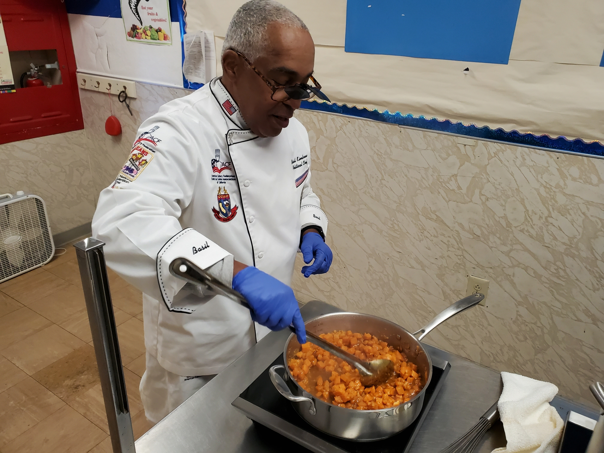 Chef Basil Kimbrew cooks sweet potatos on an SCE induction cooktop for a pre-Thanksgiving dinner for Ridgecrest Earthquake victims.