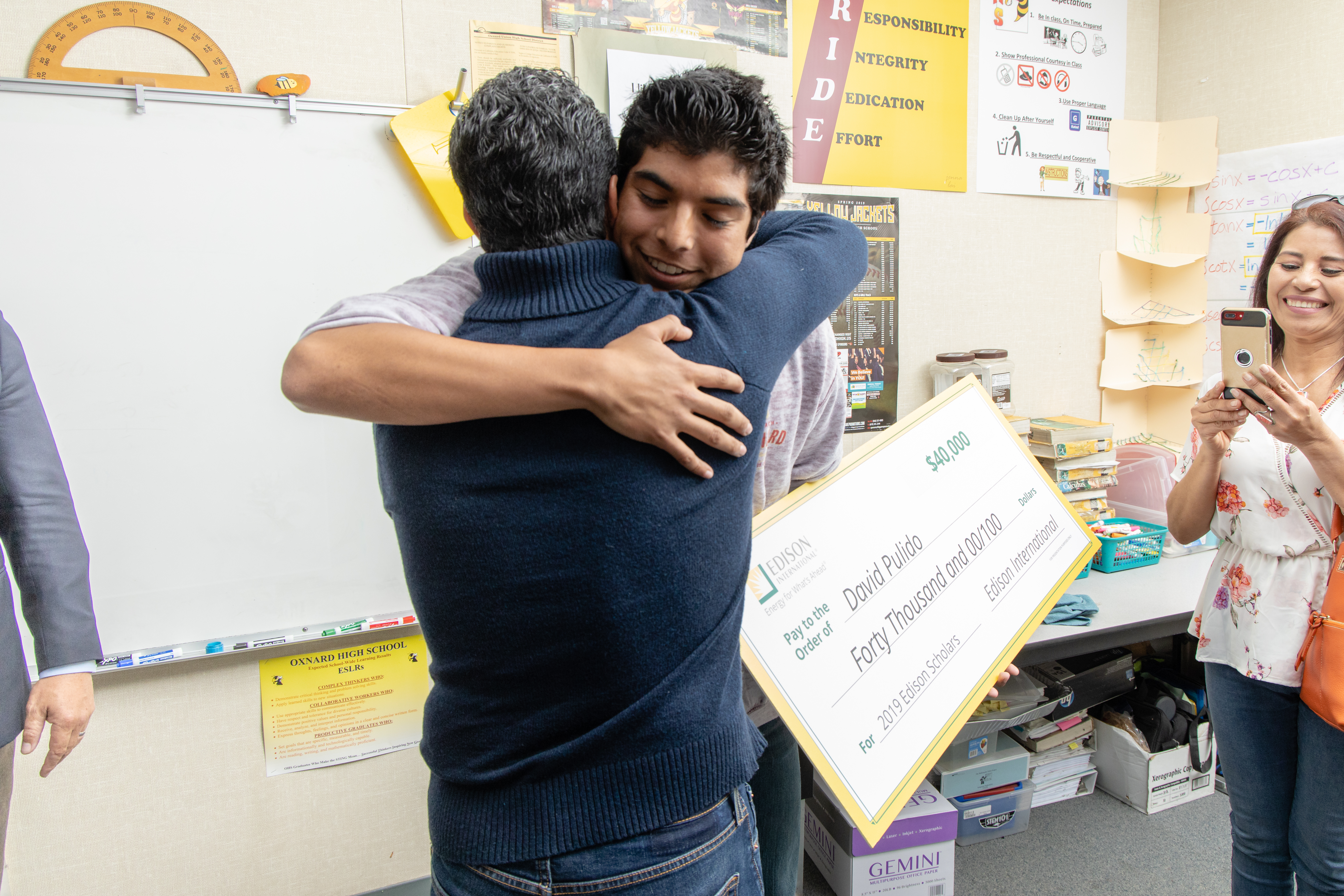 2019 Edison Scholar David Pulido hugs his dad after learning he's a 2019 Edison Scholar.