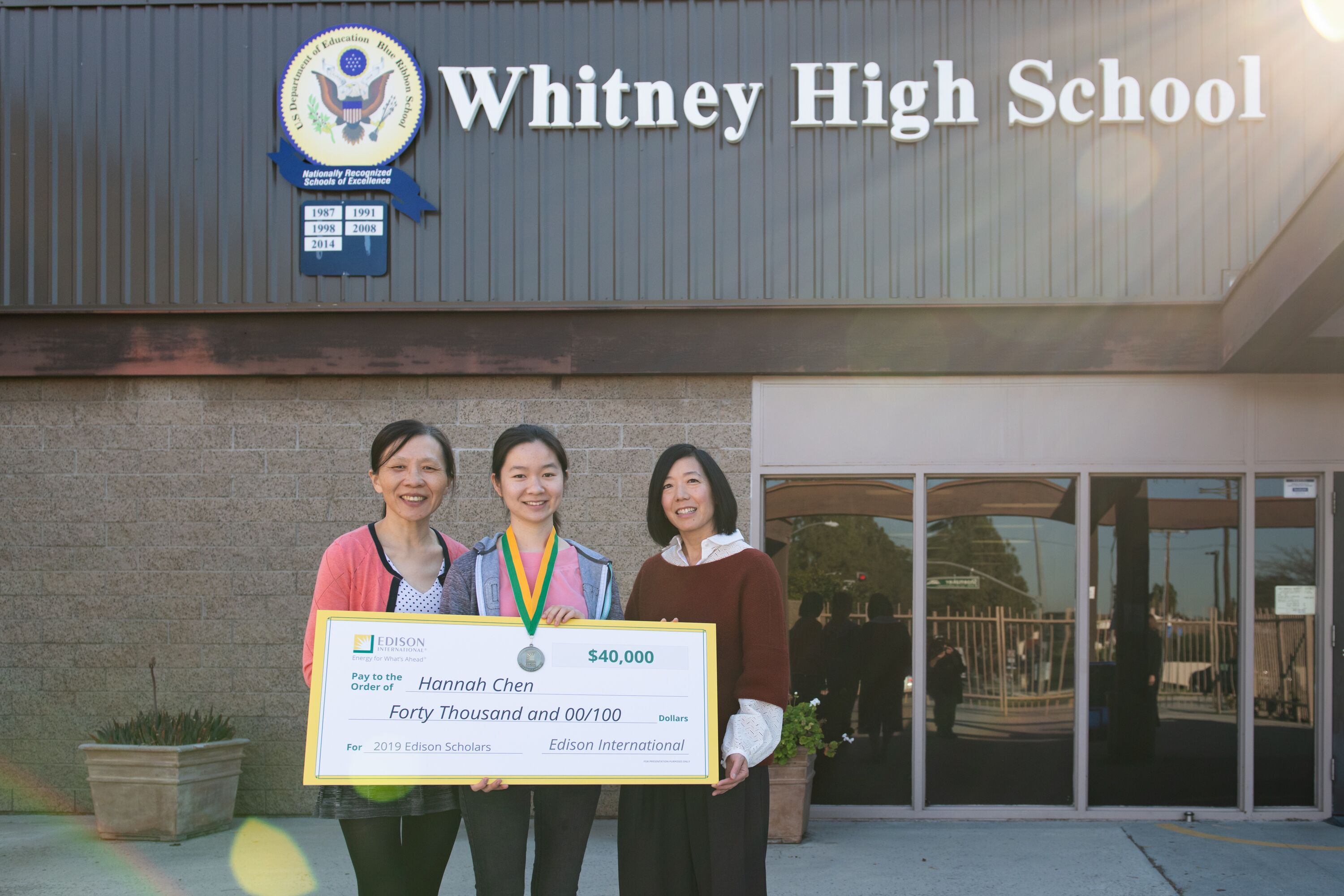 Whitney High senior Hannah Chen (center) displays her $40,000 Edison scholars check.