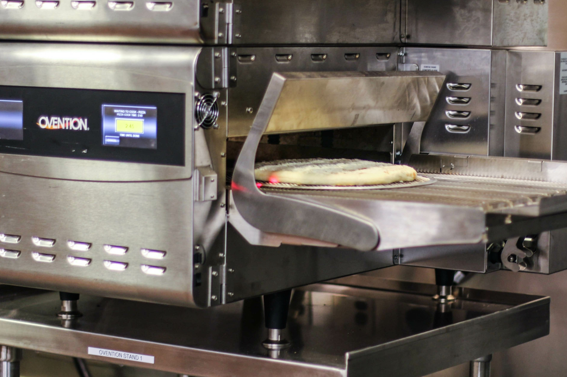 A pizza is sent through a convection oven with infrared heat during an SCE Kitchen of the Future Foodservice Technology demonstration.