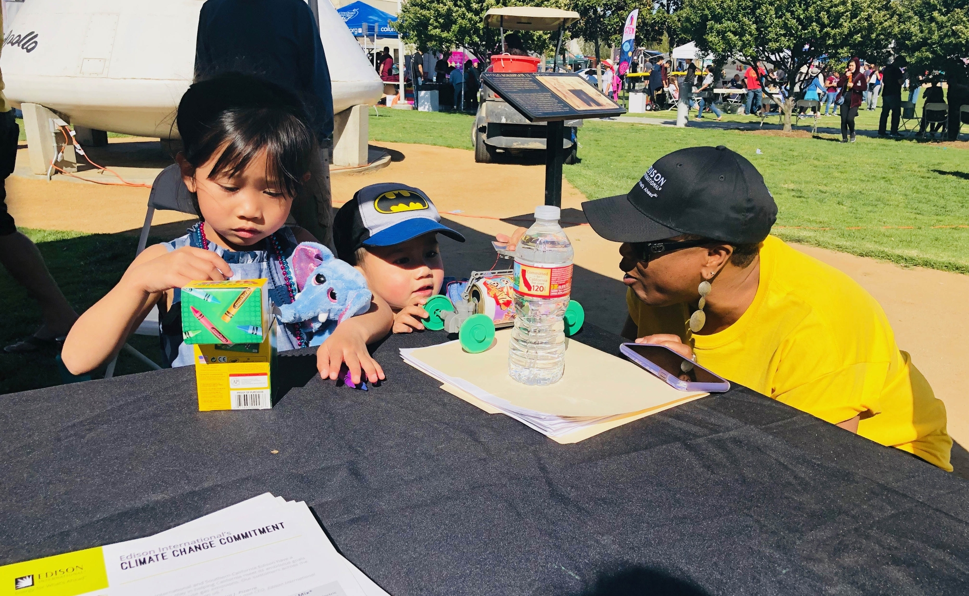 An Edison International volunteer does STEM activities with some of the festival attendees.