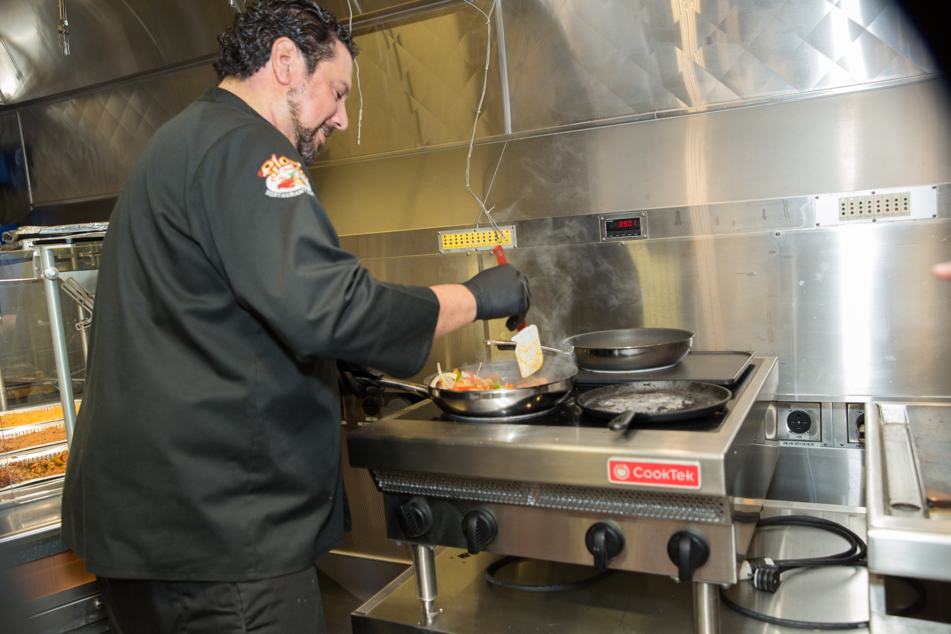 Juan Sanjuan III, owner of Gloria's Restaurant & Bar, tests out energy-efficient equipment at SCE's Foodservice Technology Center.