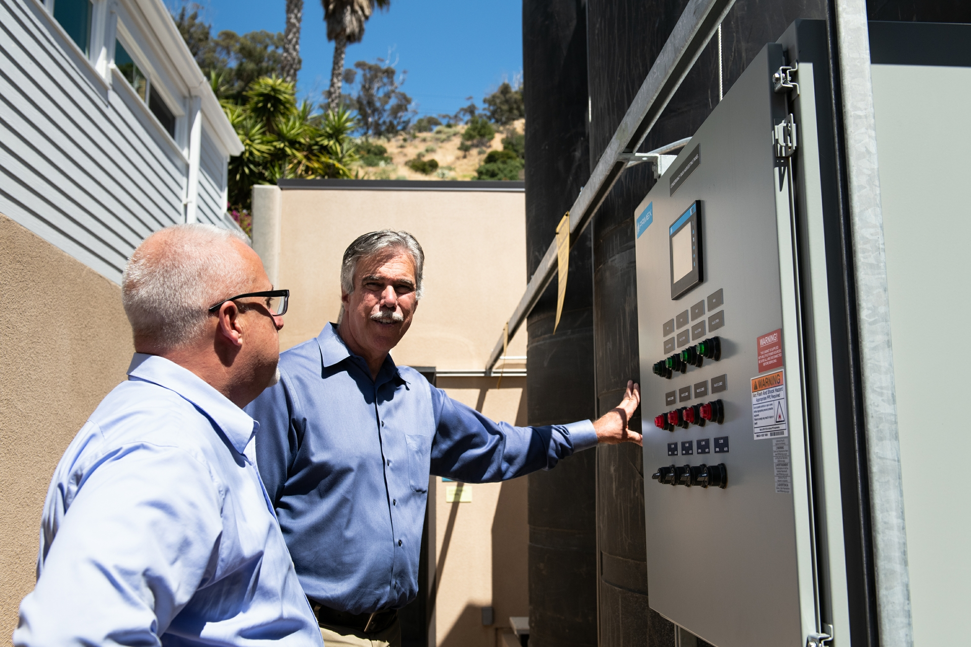 Ron Hite, SCE's island manager, and Tony Budrovich discuss the building's salt water desalination system.