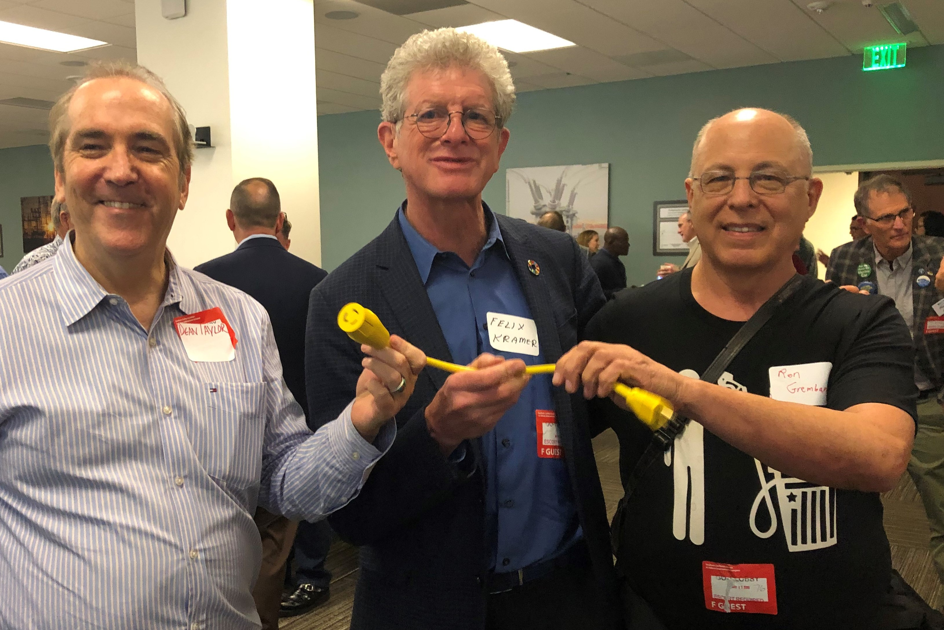 At the reunion, Dean Taylor and fellow EV advocates Felix Kramer (center) and Ron Gremban (right) of CalCars hold up the plug for their prototype plug-in hybrid.