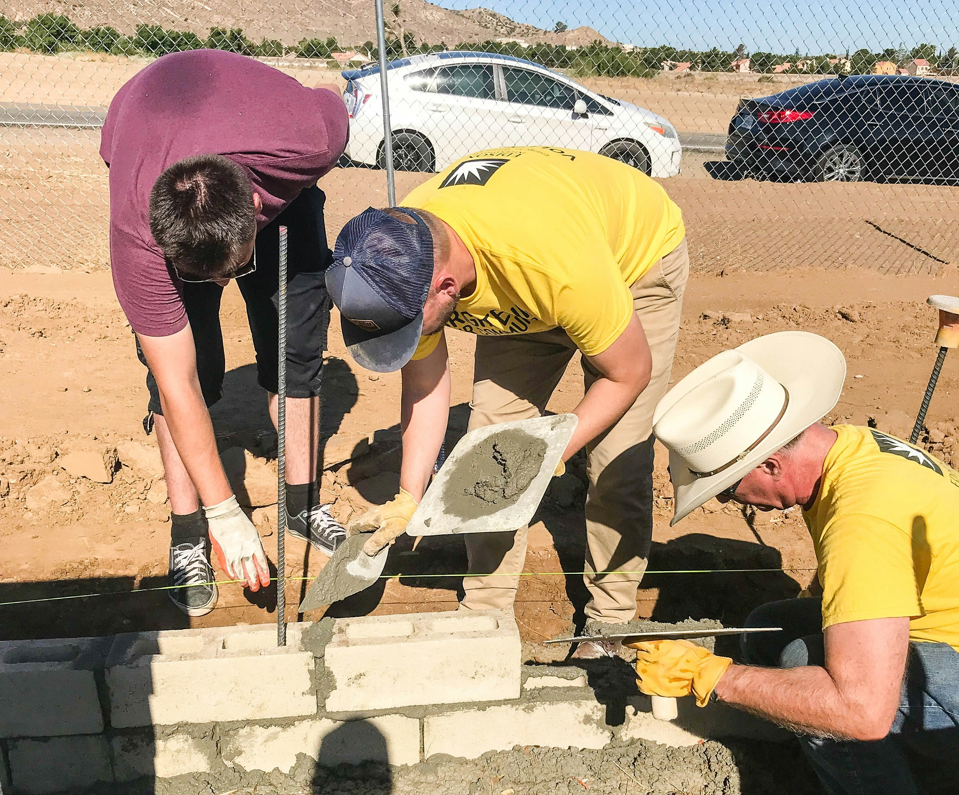 Volunteers worked together cementing blocks to construct a perimeter wall that will be part of a 56 home community for low-income veterans.