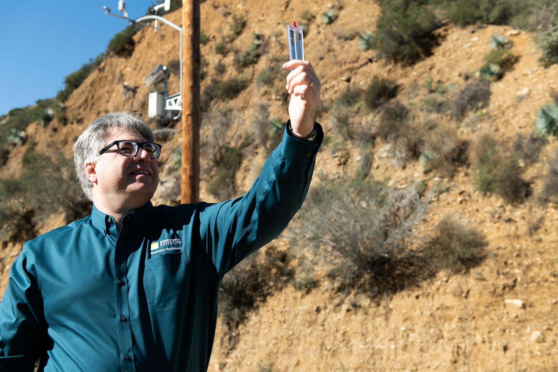 SCE fire scientist Tom Rolinski uses a hand-held Kestrel to measure wind speed.