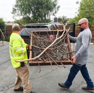 SCE workers carry a wooden platform filled with branches to attach to a power pole to provide a nesting place for ospreys.