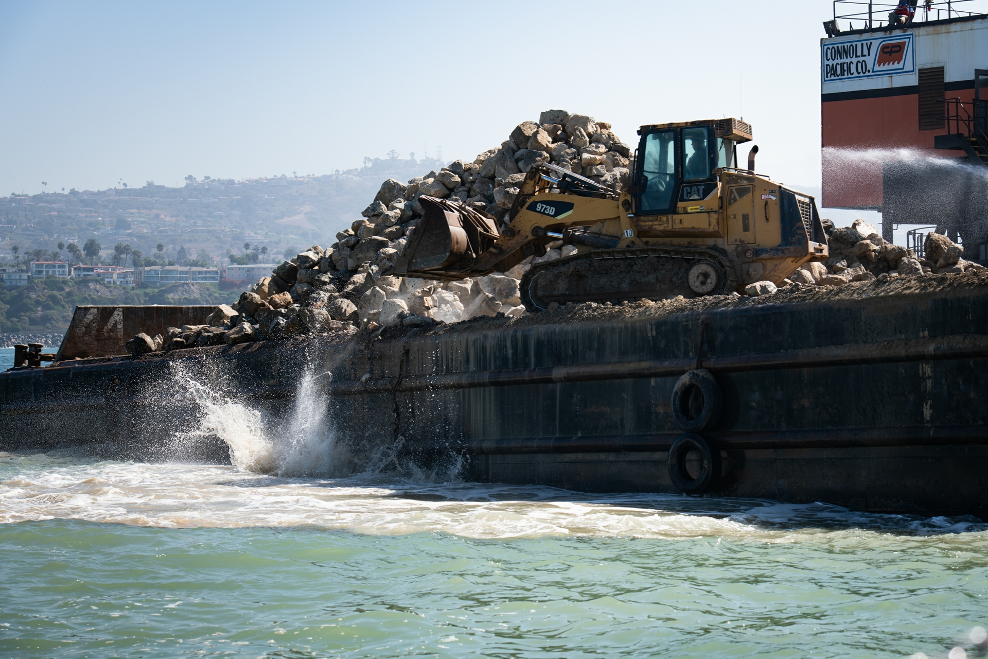 A large crane is used to pick up and drop organic quarry rocks into 38 feet of water for the expansion of the Wheeler North Reef.