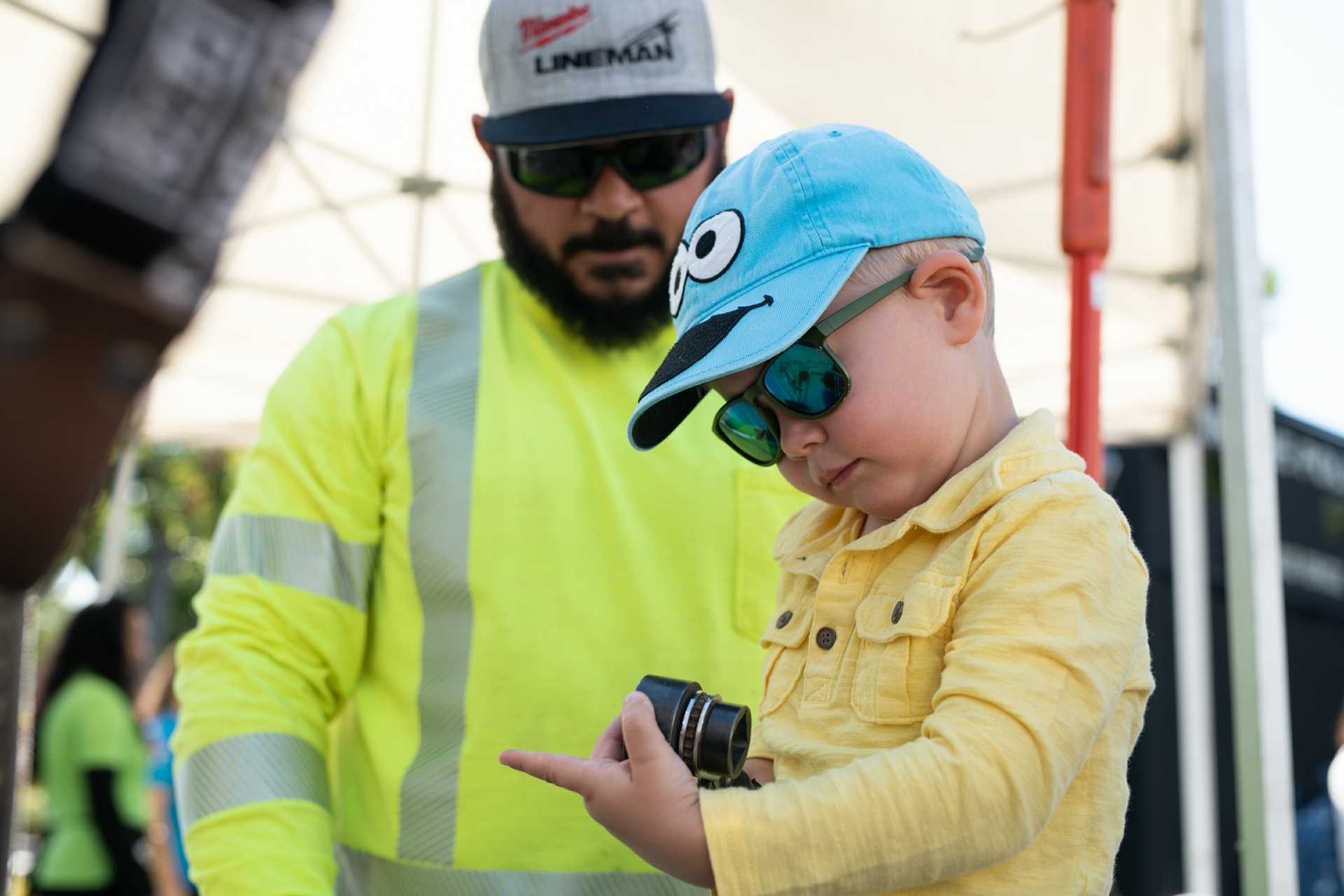 Lineman, Perry Williams, shows 4-year-old, Oliver, some of the tools that he uses on the job.