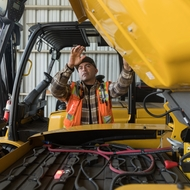Mauro Delgado lowers the hood covering the batteries of one of SCE's new electric forklifts.