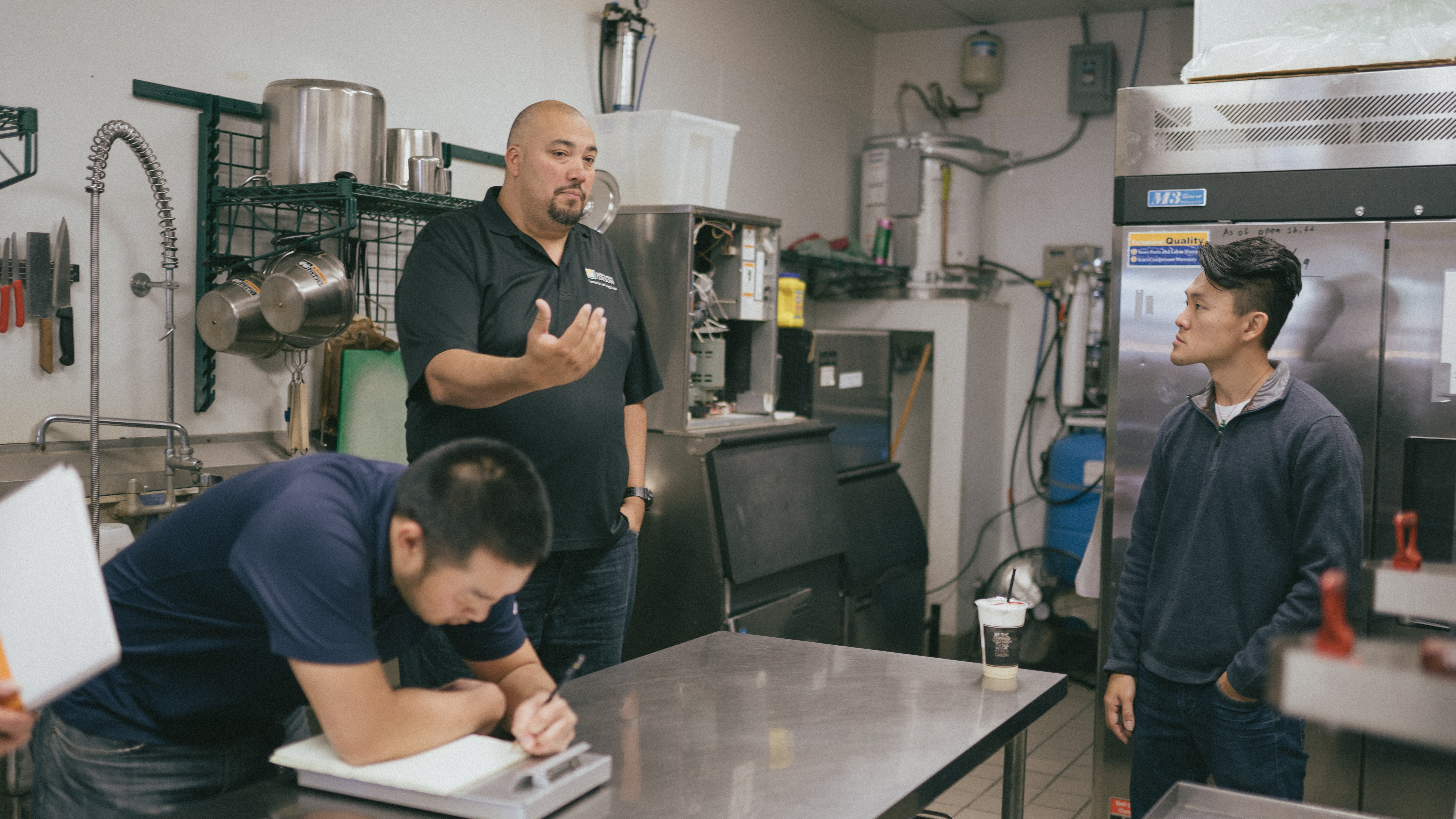 Andre Saldivar (center) with SCE's Foodservice Technology Center discusses energy efficiency with Denny Ly, co-owner of 7 Leaves.