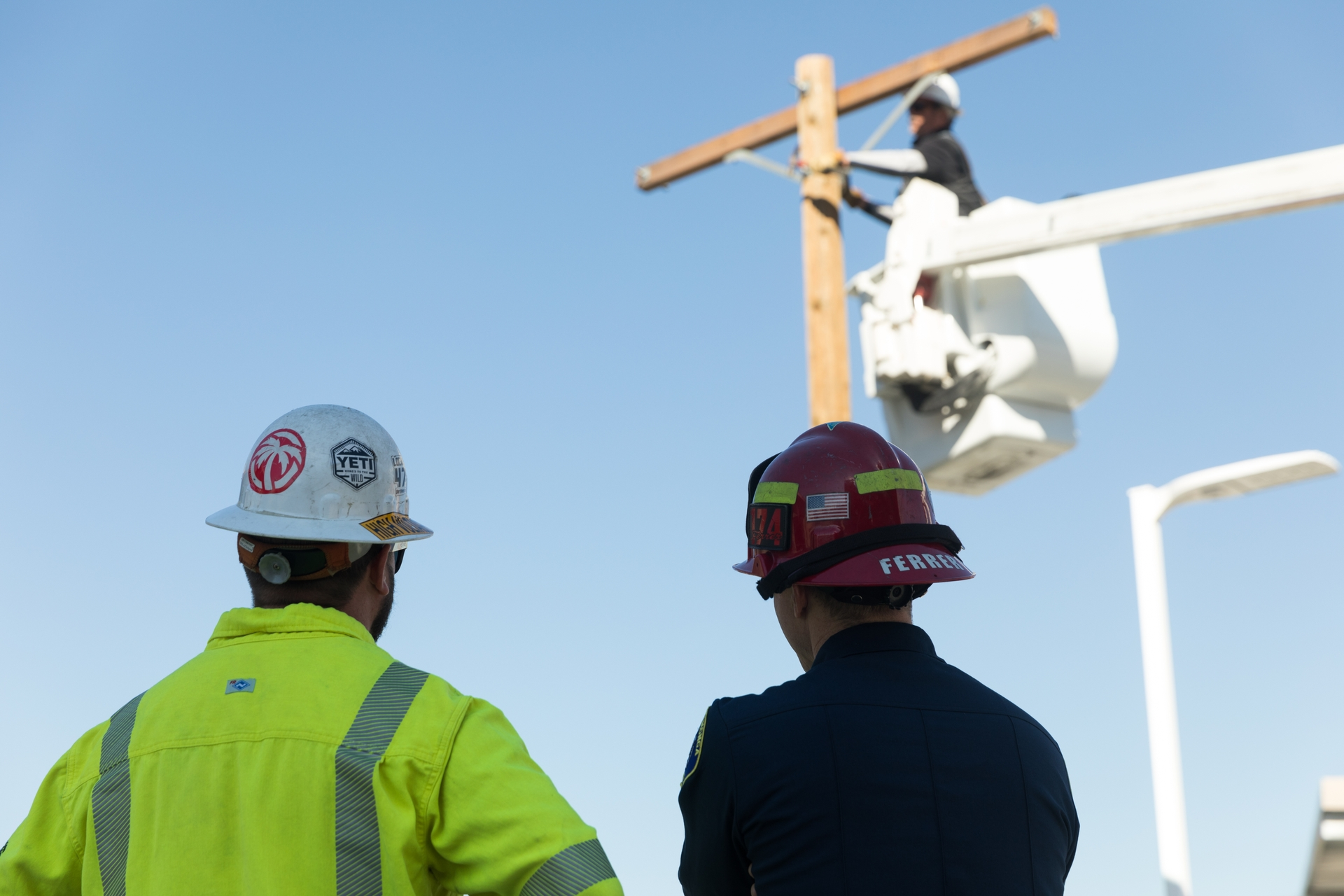 An SCE lineman and a Rancho Cucamonga firefighter look on as Lineman Richard Rocha reattaches a crossarm on a power pole.