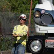 An SCE lineman prepares covered conductor to install along the utility poles.