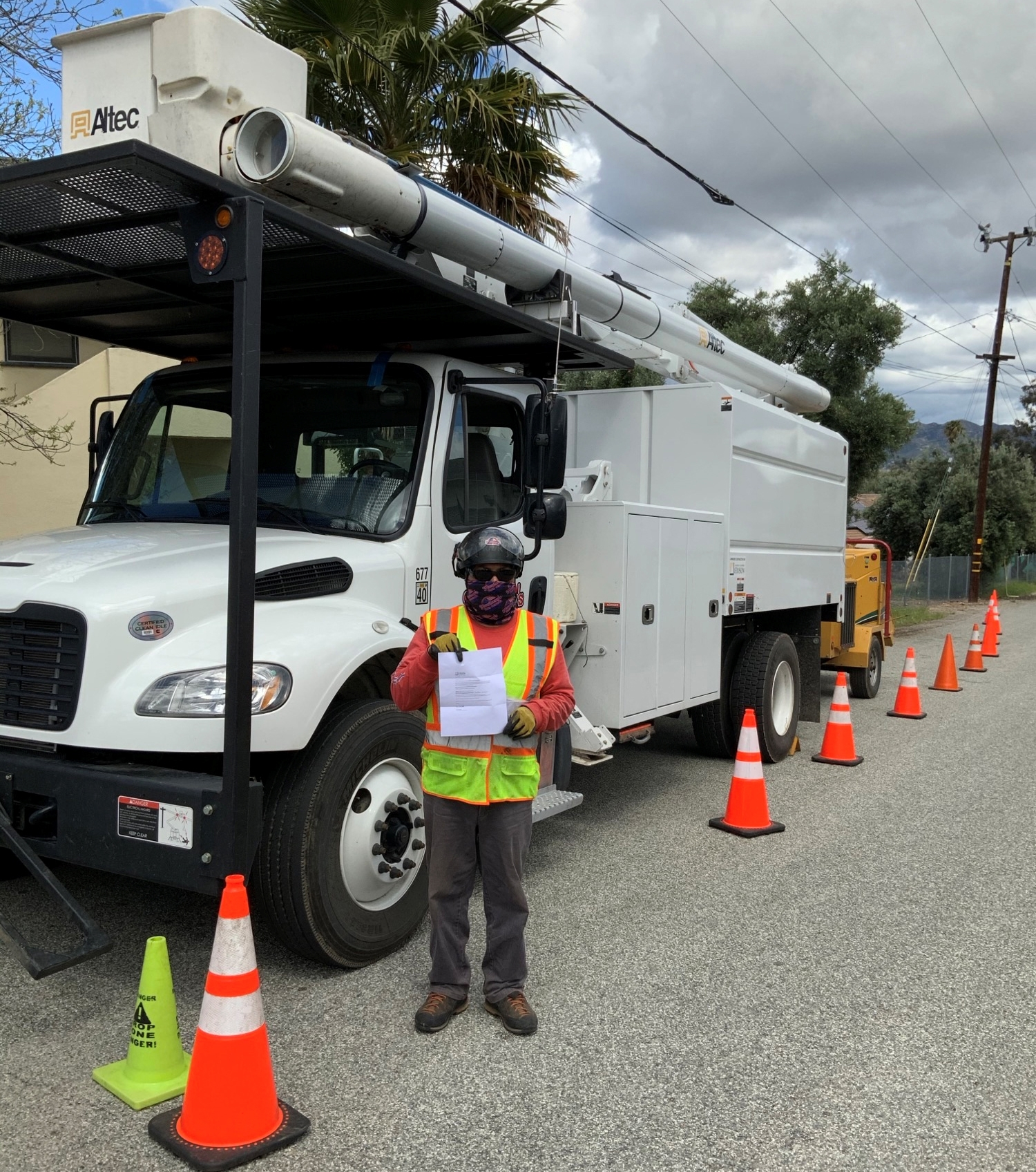 An SCE contract tree trimmer, wearing a mask for protection from COVID-19, shows a letter explaining tree trimmiing is an essential service.