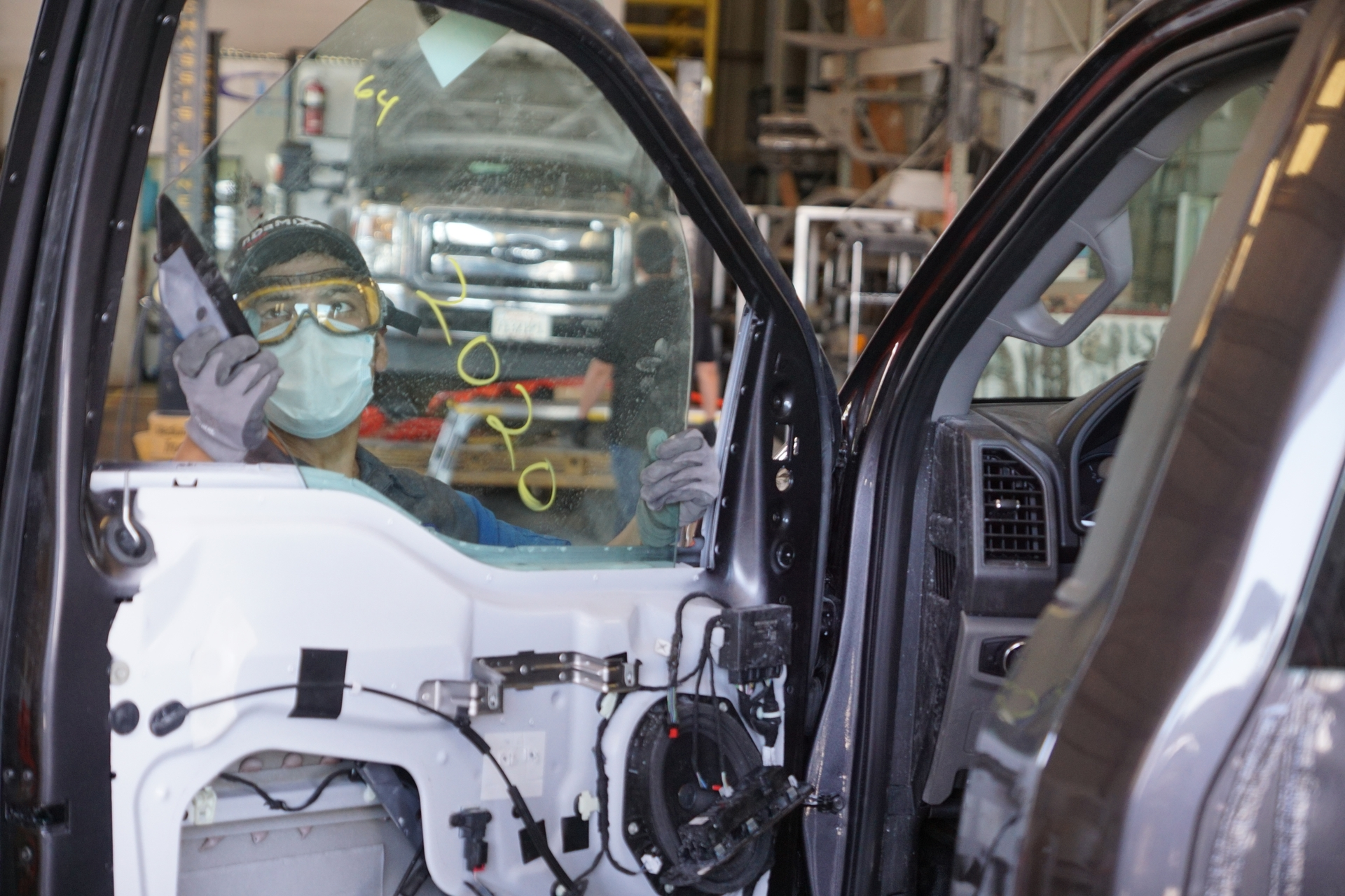 An employee at the Inland Body and Paint Center in Fontana works on an SCE truck.
