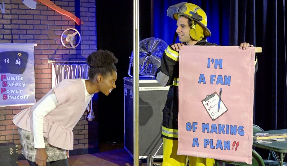 Fireman Blaze Ashman gives Penelope Planner, the heroine of the play, tips on preventing wildfires before they start, including the importance of making a plan.