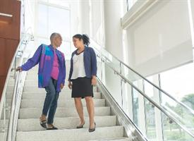 Two women standing and talking on the staircase at the Wilmot Cancer Center
