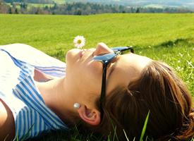 woman laying in a field with face up to the sun