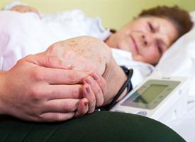 Nurse holding elderly female patient's hand as she lays in bed