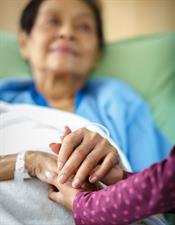elderly, sick woman in bed holding the hand of a family member