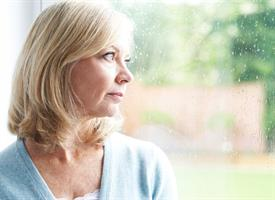 blonde woman staring out rainy window