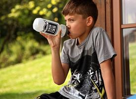 young boy drinking out of a water bottle