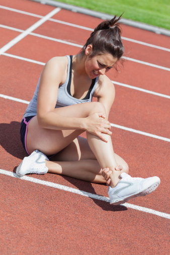 injured runner holding ankle