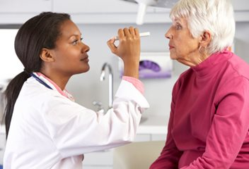 woman getting eye exam from doctor