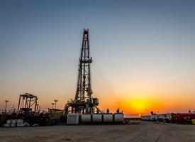 sun setting behind a fracking drill and workers