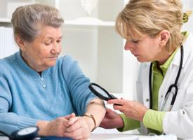 female doctor using a magnifying glass to examine a mole on elderly woman's arm