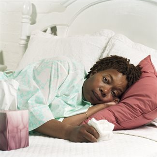 woman sick in bed with flu