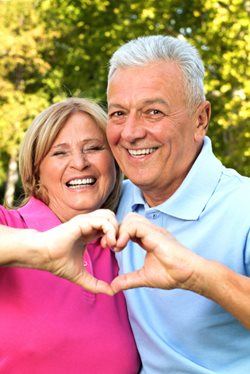 mature couple making heart symbol with their hands